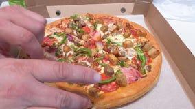 De verse pizza is in de doos De hand neemt één plak van pizza