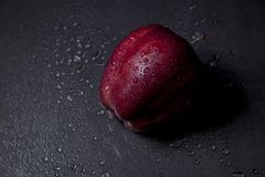 De verse rode appel met druppeltjes van water en heeft licht stock foto