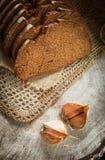 De verse rogge sneed brood op natuurlijke van het linnenservet en knoflook kruidnagels op rustieke houten achtergrond verticaal stock afbeeldingen