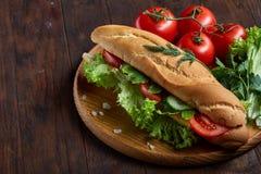 De verse sandwich met sla, tomaten en kaas diende op houten plaat over houten achtergrond, selectieve nadruk Stock Fotografie