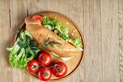 De verse sandwich met sla, tomaten en kaas diende op houten plaat over rustieke achtergrond, selectieve nadruk Stock Foto