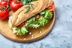 De verse sandwich met sla, tomaten en kaas diende op houten plaat over witte geweven achtergrond, selectieve nadruk Royalty-vrije Stock Fotografie