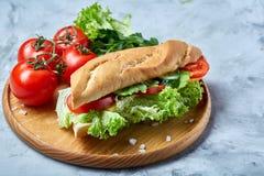 De verse sandwich met sla, tomaten en kaas diende op houten plaat over witte geweven achtergrond, selectieve nadruk Royalty-vrije Stock Afbeelding