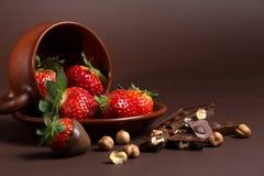 De verse sappige organische aardbeien in een oude klei werpen op een bruine achtergrond Stock Foto