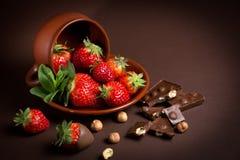 De verse sappige organische aardbeien in een oude klei werpen op een bruine achtergrond Royalty-vrije Stock Fotografie