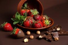 De verse sappige organische aardbeien in een oude klei werpen op een bruine achtergrond Stock Afbeelding