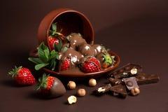 De verse sappige organische aardbeien in een oude klei werpen op een bruine achtergrond Stock Fotografie