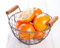 De verse sappige sinaasappelen van het de zomerbloed in een uitstekende mand met muntblad op houten lijst aangaande een witte ach Royalty-vrije Stock Fotografie