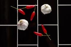 De verse Spaanse pepers van het ingrediëntenknoflook op zwarte tegelachtergrond Stock Foto's