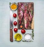 De verse stukken van ruw lam op een hakbord, met kruiden, kruiden, kersentomaten, voerden rechthoek op houten rustieke bovenkant  Stock Fotografie