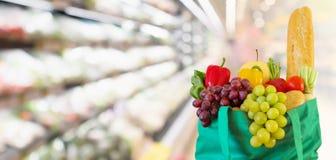 De verse vruchten en de groenten in het winkelen zak met vage de opslag van de supermarktkruidenierswinkel defocused achtergrond royalty-vrije stock foto