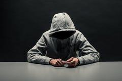 De verslaafde in grijze hoodie op het hoofd lijdt aan verslaving op DA stock foto