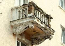 De verslechtering van het balkonbederf met zichtbare structurele bakstenen in het oude buiding van de binnenstad stock afbeelding