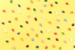 De verspreide kleurrijke snoepjes van de geleiboon op gele achtergrond stock fotografie