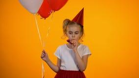 De verstoorde hoorn van de meisjes blazende partij en het houden van ballons, vierend alleen verjaardag stock footage