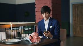 De verstoorde kerel spreekt aan zijn meisje op mobiele telefoonzitting bij alleen restaurant en wachten die dan bloemen nemen en stock videobeelden