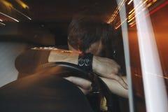 De verstoorde mannelijke bestuurder wordt gevangen drijvend onder alcoholinvloed Mens die zijn gezicht van politiewagenlicht beha royalty-vrije stock afbeeldingen