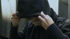 De verstoorde schooljongen in hoodiezitting op straat, liep vanaf huis, bedelaar, armoede stock videobeelden