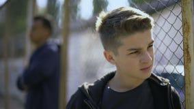 De verstoorde tienerjongens die op metaal leunen schermen, verlaten met de maatschappij, weeshuis stock videobeelden