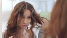 De verstoorde vrouw wat betreft droog haar be?indigt voorspiegel in badkamers Ontevreden vrouw stock videobeelden