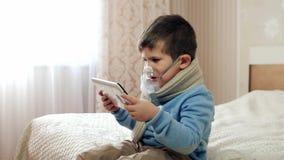 De verstuiver voor inhalatie, jong geitje met een zuurstofmasker op zijn gezicht, ziek kind ademt door verstuiver, de jongen stock videobeelden