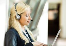 De vertegenwoordiger die van de klantendienst aan computer werken die op h spreken Royalty-vrije Stock Afbeeldingen