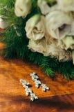 De verticaal van de zilveren oorringen met diamanten dichtbij het mooie huwelijksboeket wordt geschoten van witte rozen op de lij stock foto