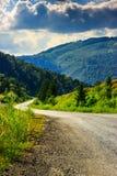 De verticale windende weg gaat naar bergen onder een bewolkte hemel Stock Afbeeldingen