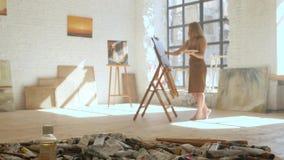 De verven van de meisjeskunstenaar op canvas op schildersezel en houdt palet in kunstworkshop stock videobeelden