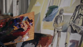 De verven van de meisjeskunstenaar op het canvas met een borstel close-up op de handen van de kunstenaar stock footage