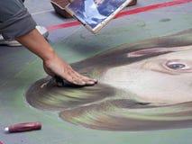De verven van de straatkunstenaar met krijt op de bestrating Stock Foto