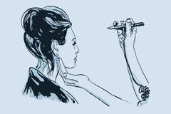 De verven van de de make-upkunstenaar van vrouwenvisagist op het gezicht van zijn cliënt met luchtpenseel Stock Foto's