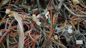 De verwarde multi gekleurde draden van oude verlaten auto's liggen in groot knoeien op een dumpende reden tot recycling stock video