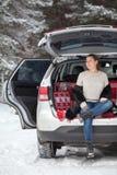 De verwarmde omhoog jonge Kaukasische vrouw knoopt binnen bontjas los zit in boomstam van eigen auto Het rusten en ademhaling in  royalty-vrije stock foto