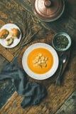 De verwarmende soep van de pompoenroom met croutons en zaden, verticale samenstelling Stock Afbeeldingen