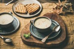 De verwarmende soep van de selderieroom en geroosterd brood over linnentafelkleed royalty-vrije stock foto