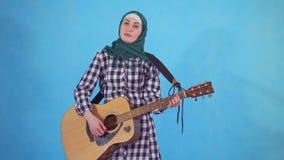 De in verwarring gebrachte jonge Moslimvrouw speelt onhandig gitaar op blauwe achtergrond stock footage