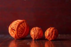 De verwarring van oranje draden voor het breien ligt op een houten lijst royalty-vrije stock fotografie