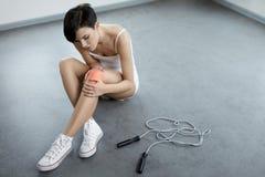 De verwonding van het been Mooie Vrouw die Pijn in Knie, Pijnlijke Knie voelen stock foto