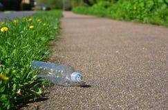 De verworpen plastic fles maakt een rommel van een voetpad of cycleway Royalty-vrije Stock Afbeelding