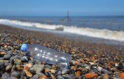 De verworpen plastic fles waste omhoog op kiezelsteenstrand Royalty-vrije Stock Afbeeldingen