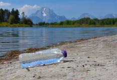 De verworpen plastic fles water maakt een rommel van een schoonheidsvlekje Stock Afbeeldingen