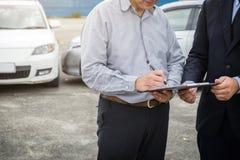 De verzekeringsagent onderzoekt Beschadigde Auto en klant die signatur indienen stock afbeeldingen