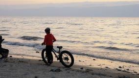 De vette fiets riep ook fatbike of vet-bandfiets in de zomer het drijven op het strand stock footage