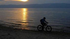 De vette fiets riep ook fatbike of vet-bandfiets in de zomer het drijven op het strand stock videobeelden