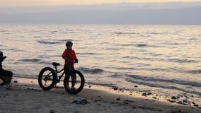 De vette fiets riep ook fatbike of vet-bandfiets in de zomer het drijven op het strand stock video