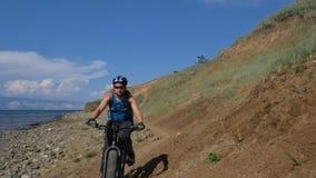 De vette fiets riep ook fatbike of vet-bandfiets in de zomer het drijven op de weg stock footage