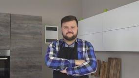 De vette gebaarde Kaukasische mannelijke kok in schort bevindt zich in de keuken en onderzoekt de camera, 4K stock videobeelden