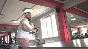 De vette gebaarde Kaukasische mens speelt pingpong en voert de sprongoefening voor gewichtsverlies uit, model stock videobeelden