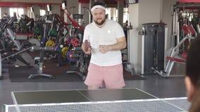 De vette gebaarde Kaukasische mens speelt pingpong en voert de sprongoefening voor gezond gewichtsverlies uit, stock video